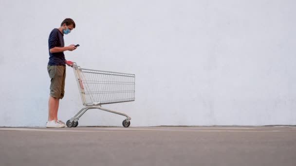 Man in a Protective Mask Standing by Supermarket. Shopping During the Coronavirus, Covid-19. Male in a Medical Mask with a Shopping Cart Go Near the Mall. Guy Reads a Shopping List on a Smartphone