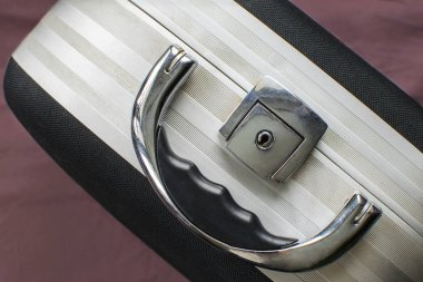 Beauty case on burgundy background. handle and lock closeup
