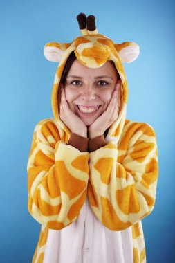 girl in a bright children's pajamas in the form of a giraffe. emotional portrait of a student. costume presentation of children's animator. Slippers in the form of cat's paws.
