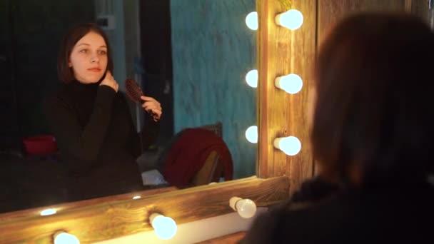 Mladá žena dívá na sebe v zrcadle v šatně. Krásný smyslnost dívka pózuje ve stylové místnosti.