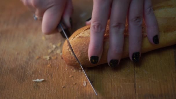 Krájení bagetu na prkénko, pomalu, velmi pomalu. Dělení bílý chléb. Krájení bagetu na stole. Tradiční francouzský chléb bageta na detail řezací stůl