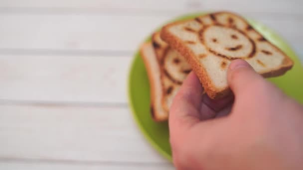 Detail of male hands spreading butter over a toasted bread slice, making a sandwich for breakfast. Selective focus on the knife and the hands