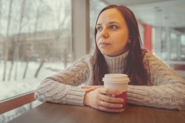 A beautiful girl dressed in a sweater holds coffee or tea in her hand and looks thoughtfully out the window.