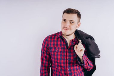 Cool man with jacket on shoulderPortrait of young handsome male in red plaid shirt holding leather jacket on shoulder against white background