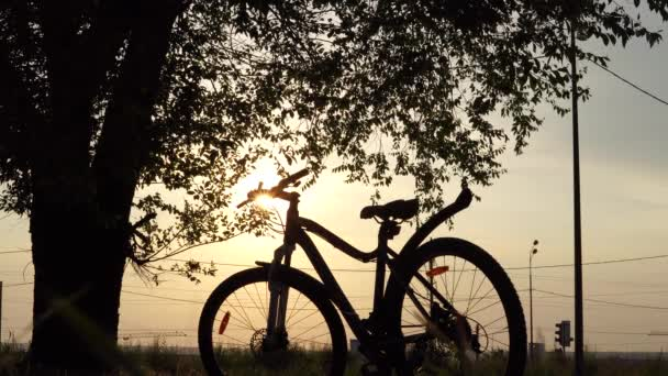 Beautiful close up scene of bicycle at sunset, sun on blue sky with vintage colors, silhouette of bike forward to sun.
