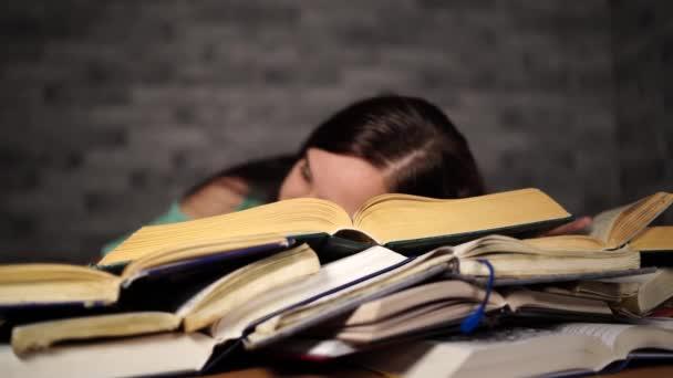 Student ženy se spoustou knih studujících na zkoušky usnul na knihách