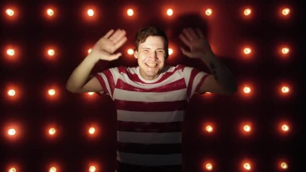 Portrait of a cheerful young man standing over red background, waving his hand