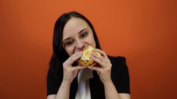 Geistloses Essen, Fast Food, ungesunde Ernährung, Überernährung, Selbstkontrolle, Hunger, Ernährungskonzept. junge Frau isst gierig großen leckeren Hamburger