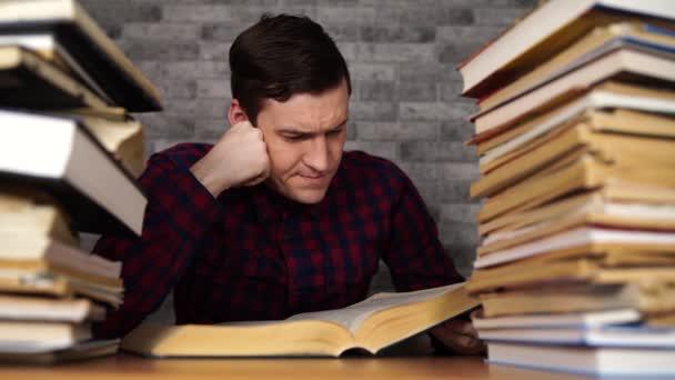 Ember diák unalmas olvasó könyvet a könyvtárban egy csomó könyvet az egyetemen.