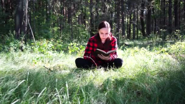 Young handsome woman reading book in open space