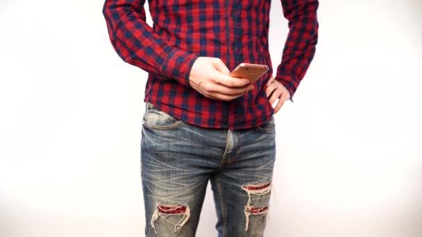 Closeup muže, který používá smartphone na bílé stěně. Ruční zasílání zpráv obchodníka s mobilním telefonem izolovaným proti Bílému pozadí.