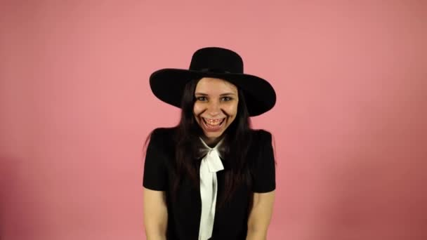 Lady smiling on a pink background. A woman in a black dress and a hat.