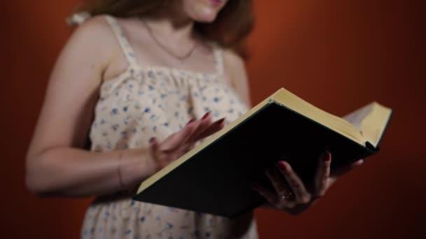 Samice čte knihu stojící na oranžovém pozadí. Žena prolistuje velkou knihou