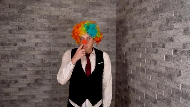 Egy férfi piszkálja az orrát munka közben. Irodai munkás bohóc parókában, bohóc koncepció a munkahelyen. Üzletember bohóc parókával. Eredeti bohócjelmez Halloweenre