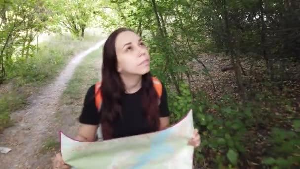 Žena s batohem a mapou. Cestovatel cestuje sám