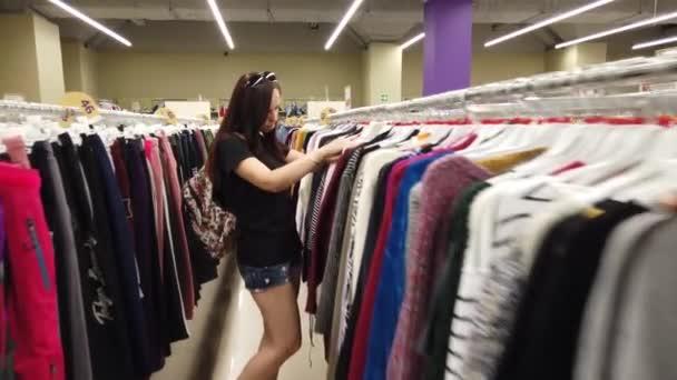 Dívka v obchodě hledá oblečení ke koupi. Mladá žena nakupuje oblečení