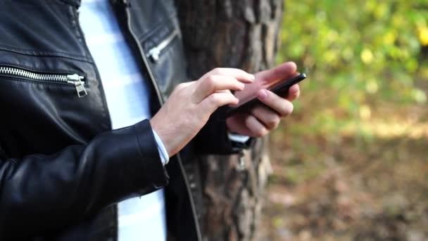 Chlápek v kožené bundě na ulici, píše zprávu na smartphone. Muž s telefonem