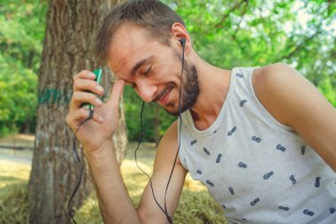 A young handsome man with beard in a t-shirt is sits in the hay, listens to music and sings in the park.