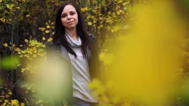 Portrét krásné usměvavé ženy stojí v podzimním lese mezi větvemi stromů se žlutým listím.
