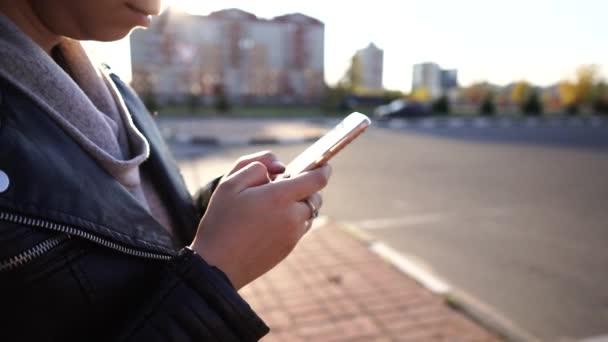 Žena píše zprávu pomocí chytrého telefonu, když stojí