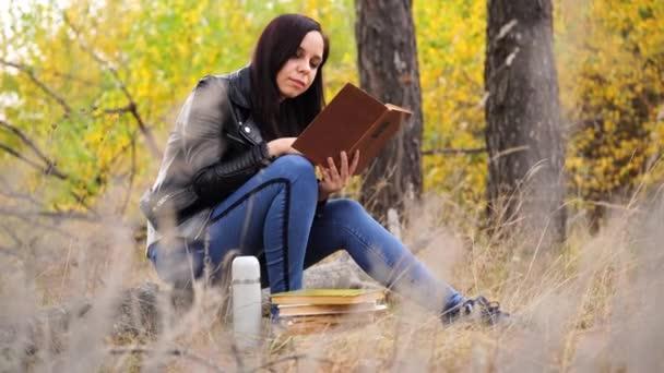 Egy fiatal, gyönyörű nő hosszú, sötét hajjal alkalmi ruhában ül egy fatörzsön és könyvet olvas az őszi erdőben..