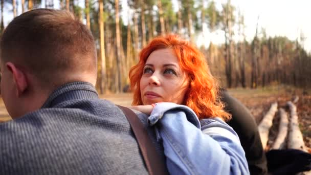 Portrait of a married couple in the autumn forest. The woman leaned thoughtfully on the mans shoulder.