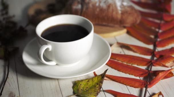 Kouřící šálek kávy s kávovými zrny a croissantem na starožitném dřevěném stole. Domácí croissant podávaný s černou kávou nebo americano. Káva přestávka s lahodným croissant. Podzimní skladba