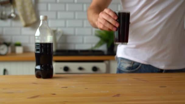 Egy férfi kezéről, amint egy pohár limonádét iszik a konyhában. Kólát iszik, szomját oltja..