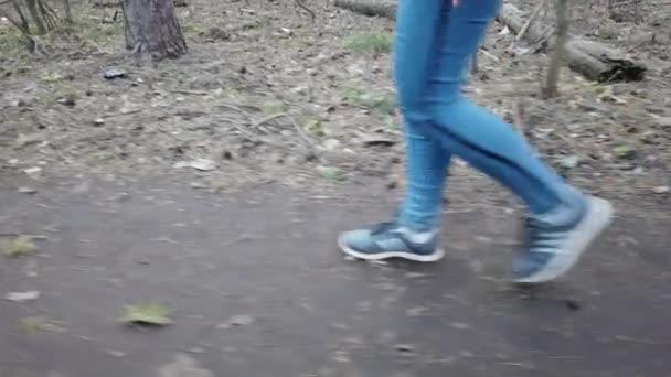 Ein Mädchen in blauen Jeans und Turnschuhen geht durch den Wald, in Großaufnahme an den Füßen. Eine Touristin geht auf einem schmalen Waldweg.