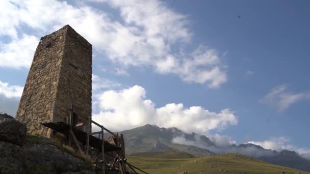 Staré kamenné věže v zeleném hornatém terénu. Starobylé kamenné budovy starého města se nachází na zeleném kopci proti horám pokrytým lesy a mlhou v letních dnech.