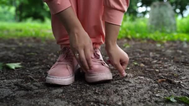 Großaufnahme einer Frau, die ihre Schuhe putzt. Frau in rosa Turnschuhen steht im Sommer im Park