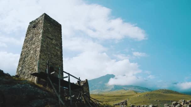 Stará kamenná věž v zeleném hornatém terénu. Starobylá kamenná budova starého města se nachází na zeleném kopci proti horám pokrytým lesy a mlhou v letních dnech