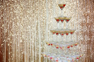 Sparkling champagne pyramid, tower of glasses at the party in front of golden wall