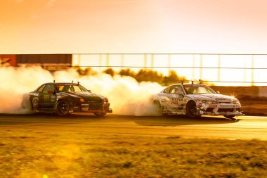 MOSCOW, RUSSIA - MAY 05, 2018: cars are drifting at motordrome in the light of sunset, first stage of Russian Drift Series 2018, Moscow Raceway motordrome