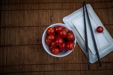 cherry tomatoes in a white chinese bowl with chopsticks and a square plate