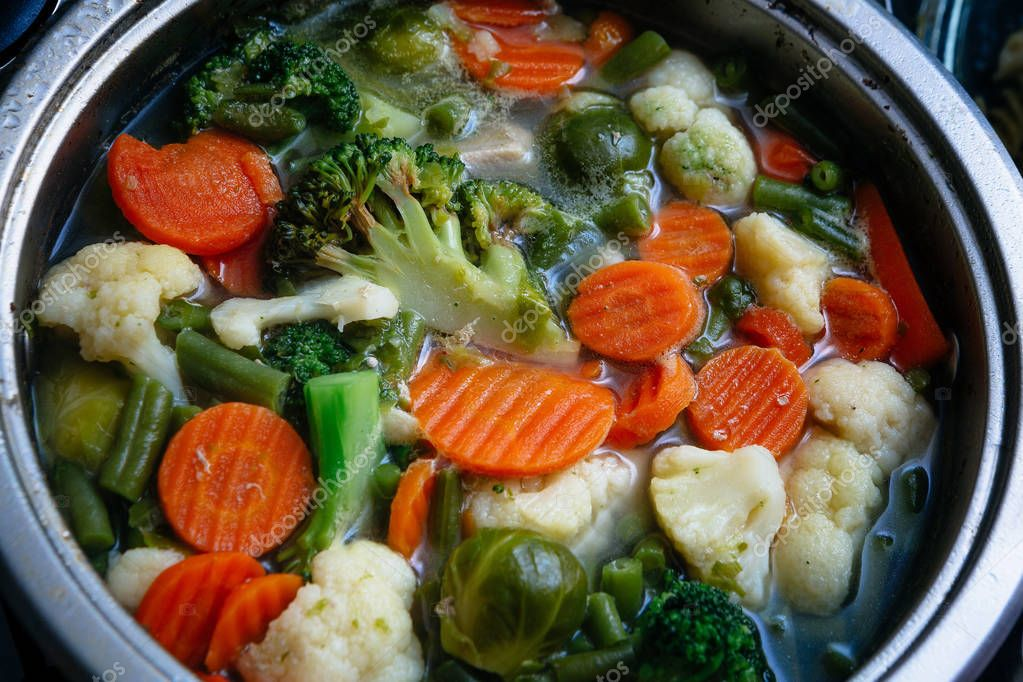 colored vegetable soup boiling in a shiny metal pan