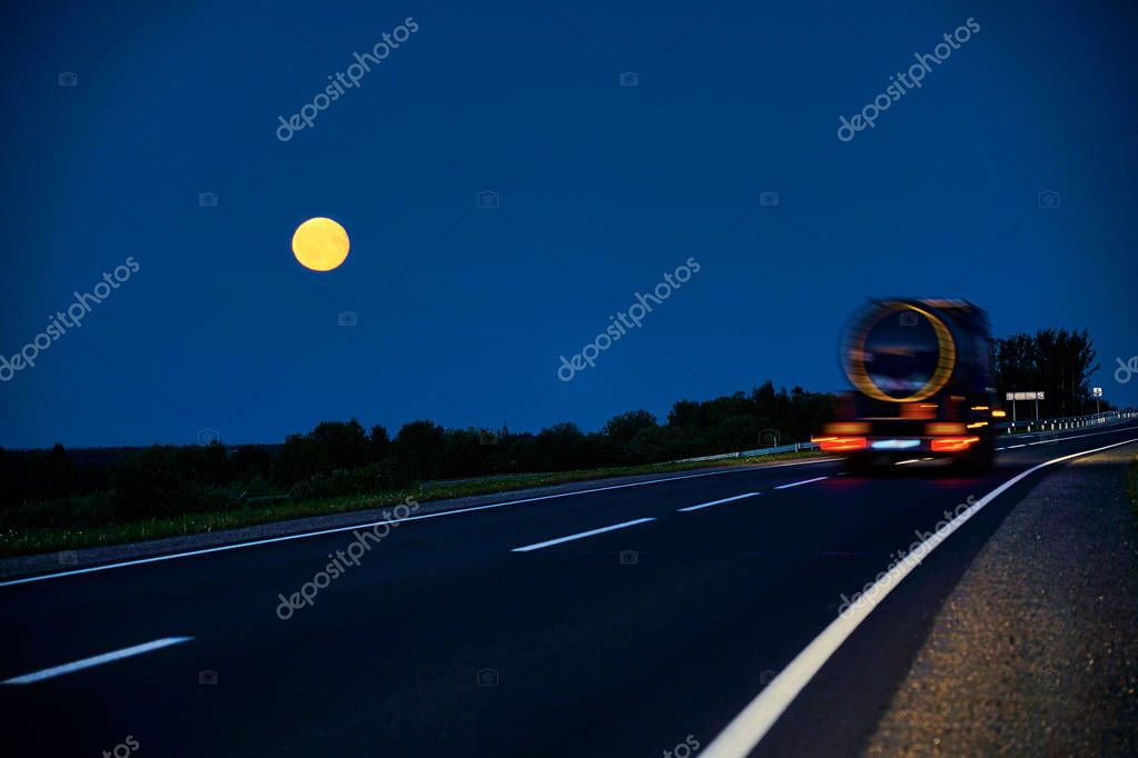truck driving on country road by moonlight