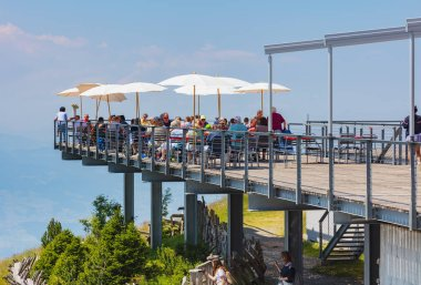 Mt. Rigi, Switzerland - July 19, 2018: people at a restaurant on the top of Mt. Rigi in summer. Mt. Rigi is a popular tourist destination, accessible by a standard-gauge rack railway operated by the Rigi-Bahnen AG company.