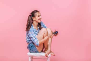 Girl with playing computer games with joystick on pink backgroun