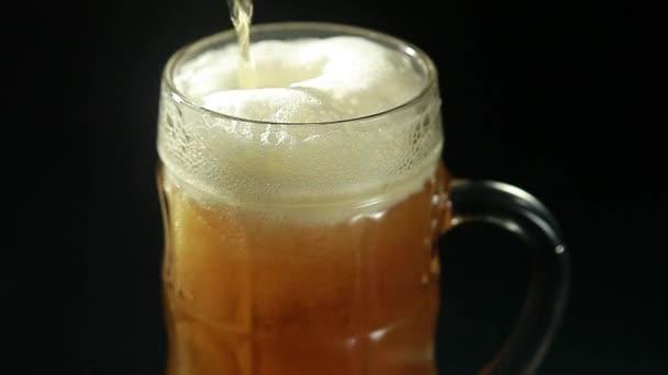 Pivo se nalije do sklenice na černém pozadí zblízka