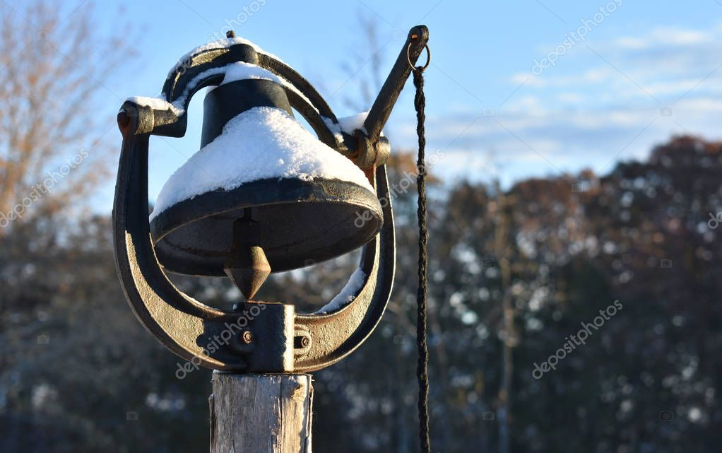 an old black dinner bell with snow on it