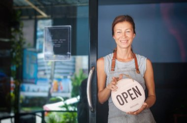 Woman waitress apron, cafe owner standing in the doorway, holding a sign with Open waiting for customers. Small business concept, cafes and restaurants