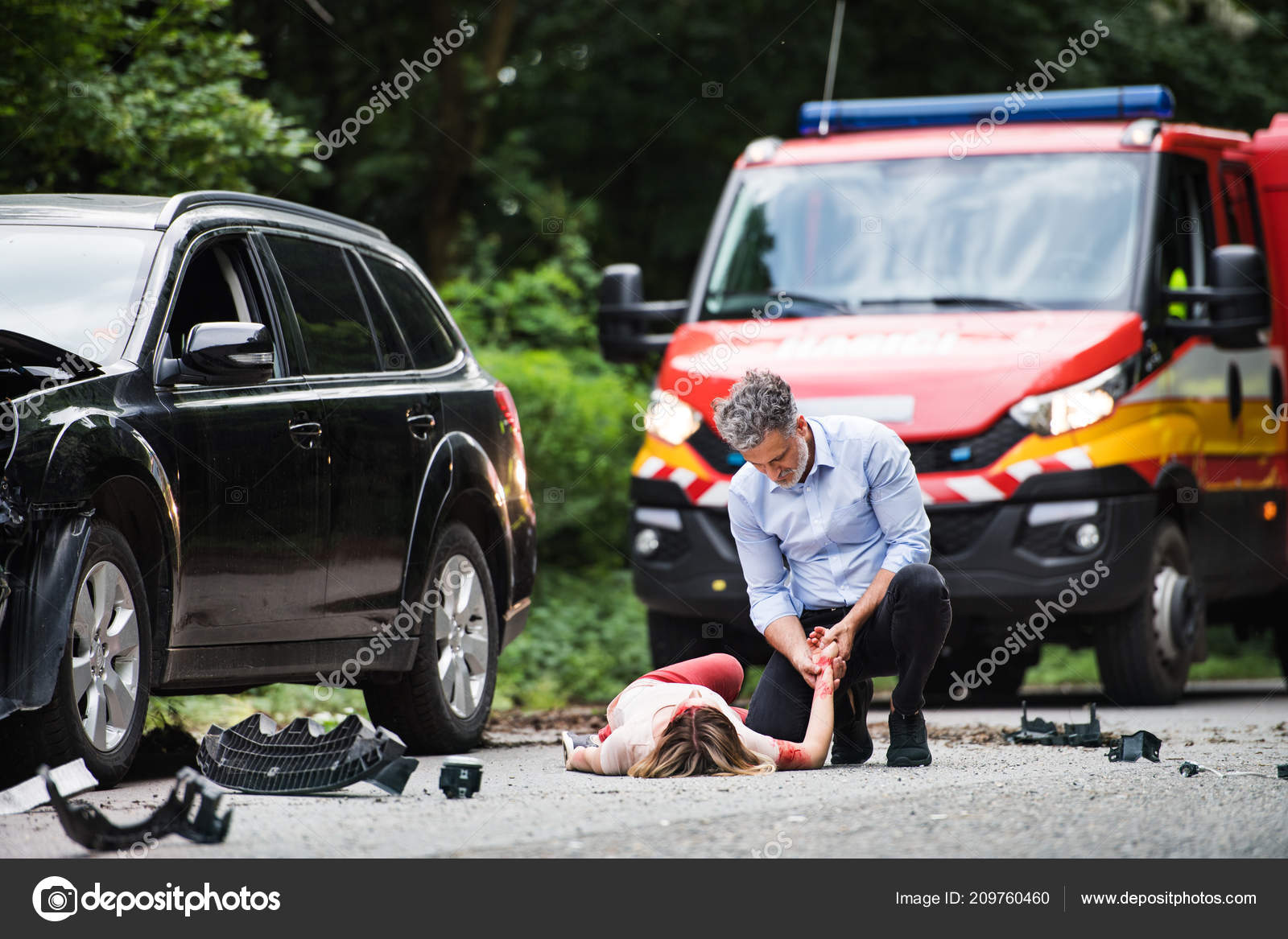 A man helping a young woman lying unconscious on the road