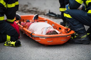Firefighters putting an injured woman into a plastic stretcher after a car accident.