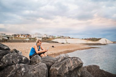 Young sporty woman runner with earphones and smartphone sitting outside on the beach in nature, listening to music and resting.