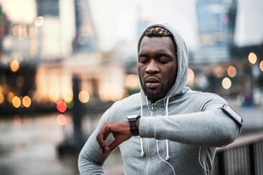 Black man runner with smartphone in an armband on the bridge in London, resting.
