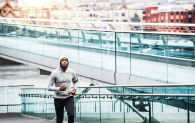 Young sporty black man runner running on the bridge outside in a city.
