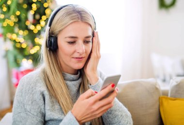 A young woman with headphones and smartphone at home at Christmas time.