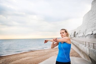Young sporty woman runner with earphones standing outside on the beach in nature, listening to music and stretching. Copy space.