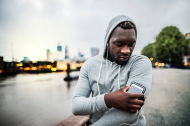 Black man runner with smartphone in an armband on the bridge in a city, resting.
